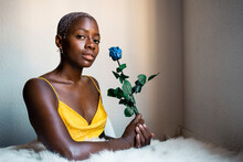 Confident Female Hipster Sitting With Blue Rose Against Wall At Home