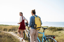 Young Man And Woman With Bicycles Walking On Footpath Against Clear Sky