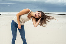 Cheerful Woman With Hand In Hair Standing At Beach