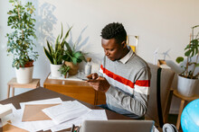 Male Financial Advisor Taking Photo Of Account Document On Desk At Home Office