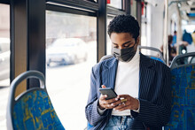 Young Businesswoman Using Mobile Phone In Bus During COVID-19