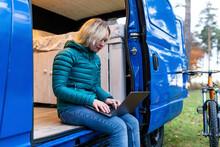 Blond Woman Working On Laptop While Sitting At Door Of Camper Van