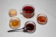 A Cup Of Strong Tea, Rosettes With Raspberry Jam, Apples And Honey. White Background.