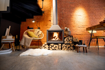 Cozy fireplace with firewood in the loft style home interior with brick wall background, burning fire in the fireplace, house coziness in winter