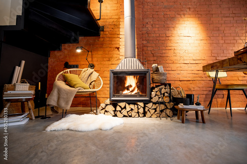 Slika na platnu Cozy fireplace with firewood in the loft style home interior with brick wall bac