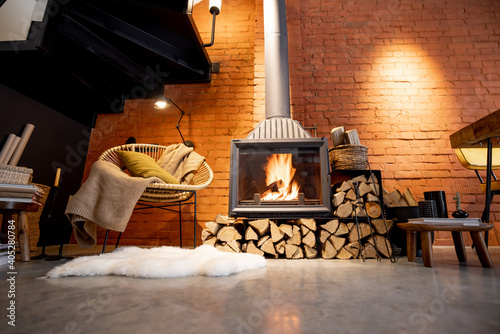 Fotografie, Obraz Cozy fireplace with firewood in the loft style home interior with brick wall bac