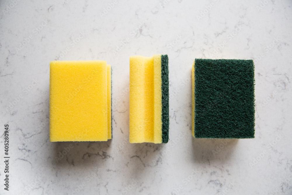 Fototapeta Kitchen sponges on a marble kitchen counter, top view.