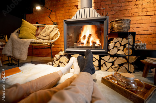 Couple lying by the burning fireplace in a cozy house in loft style