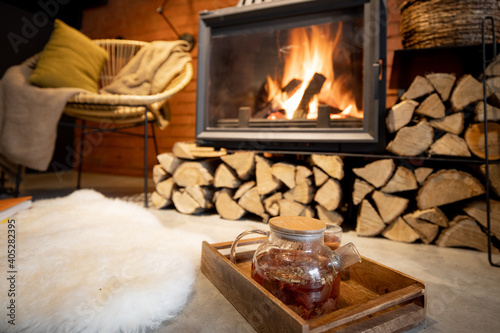 Fototapeta Cozy place by the fireplace with firewood, hot drink and sheepskin in a beautifu