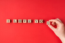 I Love You Concept. Above Close Up Flat Lay View Photo Of Female Hand Writing Phrase Using Wooden Blocks Isolated Bright Color Backdrop