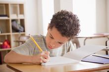 Schoolboy Writing In Notebook