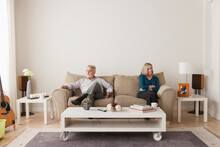 Angry Senior Couple Sitting On Sofa