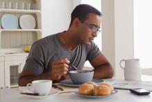 Mature Man Eating Breakfast And Reading Newspaper