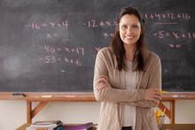 Portrait Of Teacher With Blackboard In Background
