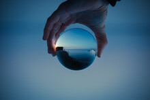 Blue Sky With A Clear Lake In Crystal Glass Ball Holding In Hand