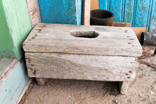 A Dilapidated Wooden Stool With A Hole In The Seating Area On The Concrete Floor Near The Village House