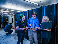 Three Co-workers Looking At A Tablet In Data Center
