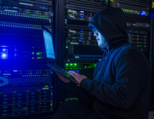 Hacker Holds Laptop Next To Server Racks