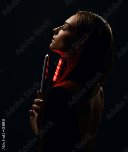 Profile of young beautiful woman with long silky straight hair in black body with eyes closed holding hair straightener in hand over dark background. Haircare, beauty, wellness concept