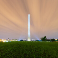 USA, Washington DC, Cloudy Sky Over Lawn In Front Of Washington Monument At Dusk