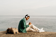 Young Man With Headphones Writing In Diary By Sea