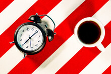 Mug Of Coffee And Alarm Clock On White And Red Striped Pattern