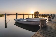 Germany, Schleswig-Holstein, Hemmelsdorf, Rowboats Moored To Pier On Shore OfHemmelsdorferSee Lake At Sunrise