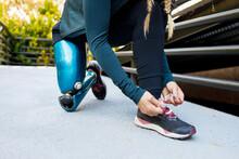 Athlete With Prosthetic Leg Tying Shoe Lace While Kneeling On Bridge