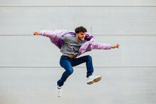 Carefree Young Man With Arms Outstretched Jumping Against Gray Wall