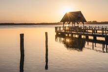 Germany, Schleswig-Holstein, Hemmelsdorf, Sun Rising Over Empty Pier On Shore Of Hemmelsdorfer See Lake