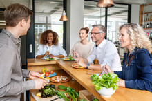 Smiling Business People Having Food On Kitchen Counter In Office
