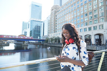 Businesswoman With Backpack And Headphones Using Mobile Phone While Standing On Bridge In City