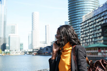 Smiling Female Professional On Phone Call In City During Sunny Day