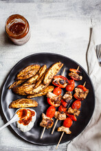 Gyros Chicken Skewers With Tomatoes, Bell Peppers, Potato Wedges In Plate By Tzatziki On Table