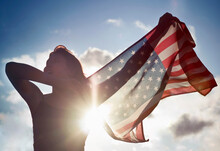 Woman Holding American Flag In Sky