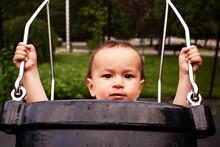 Portrait Of Baby Boy Sitting In Park Swing