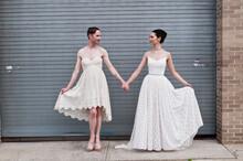 Gender Fluid Model And Female Model Showing Off Cotton Wedding Dresses