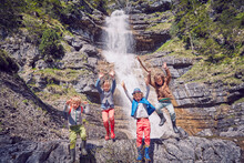 Group Of Children Jumping Off Rocks By Waterfall