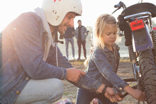 Young Girl Helping Her Father Fix Wheel On Moped, Outdoors