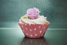 Still Life Of Iced Cupcake In Pink Spotted Case