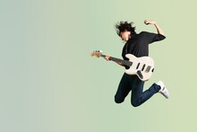 Portrait Of A Musician Man Jumps While Playing On Guitar
