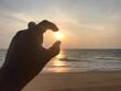 Leinwandbild Motiv Optical Illusion Of Woman Hand Holding Sun At Beach During Sunset