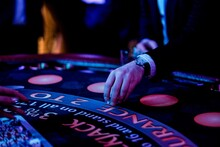 Cropped Hands Of People Gambling In Casino