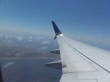Airplane Flying Over Ocean Against Blue Sky