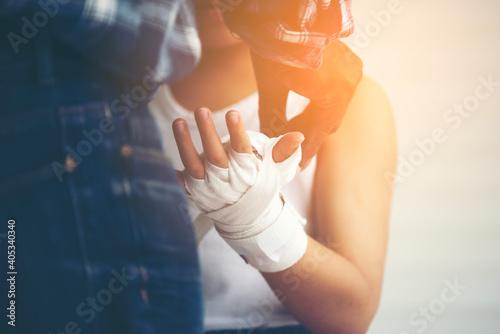 Billede på lærred Midsection Of Man Wrapping Bandage Around Hand While Standing Against Gray Backg