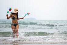 Full Length Of Woman Holding Pinwheel Toys While Walking At Beach