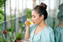 Beautiful Asian Woman Having Morning Tea At Balcony