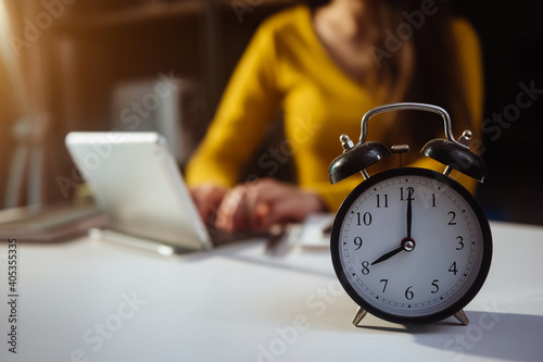 Obraz Alarm clock on the desk. Business working in modern office building or home at night using laptop.. at office. - fototapety do salonu