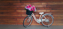 Bicycle With A Flower Basket In Pastel Colours Isolated With Wooden Background