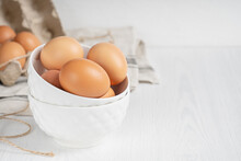 Raw Brown Organic Chicken Eggs In China Saucers And Recycled Paper Container On White Wooden Background. Healthy Eating And Sustainable Consumption Concept. Image With Copy Space, Horizontal